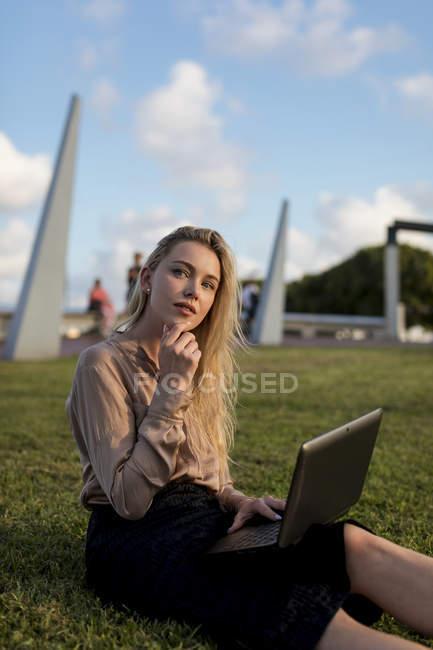 Молода комерсантка сидить на луці, використовуючи ноутбук. — стокове фото