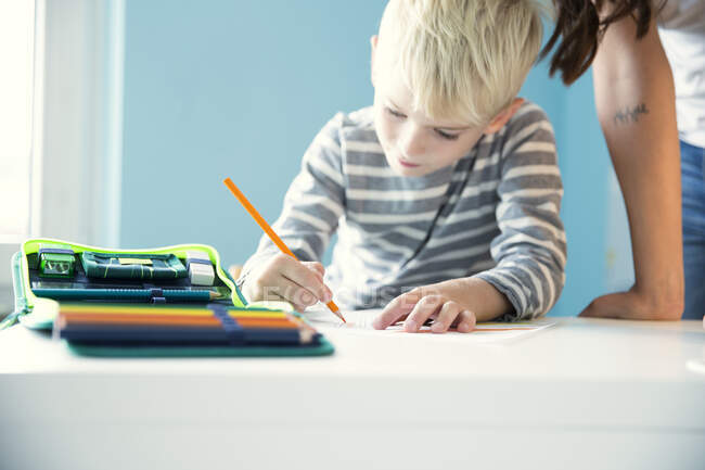 Boy doing homework with mother leaning on desk — Stock Photo