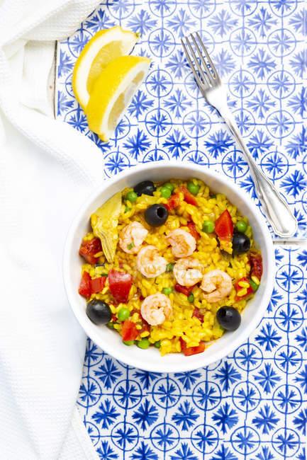 Paella con riso, peperone, pomodoro, carciofo, pisello, oliva nera, curcuma e gamberetti — Foto stock