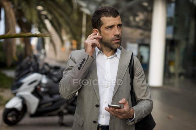 Бизнесмен с мобильным телефоном в городе надевает наушники — стоковое фото