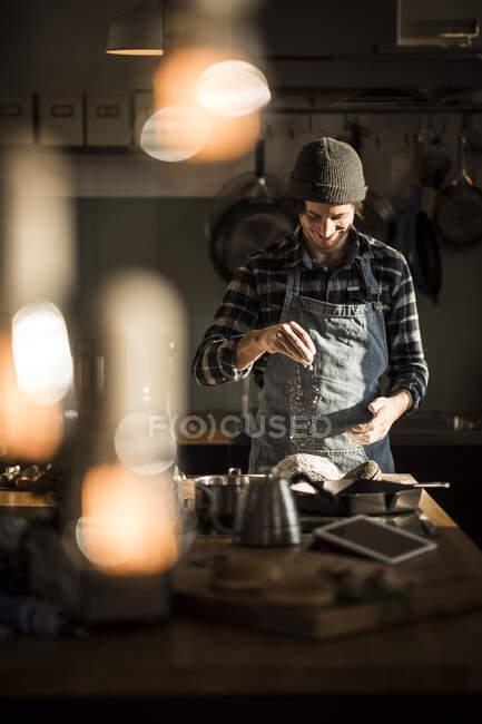Un homme prépare de la pâte à pain dans sa cuisine — Photo de stock