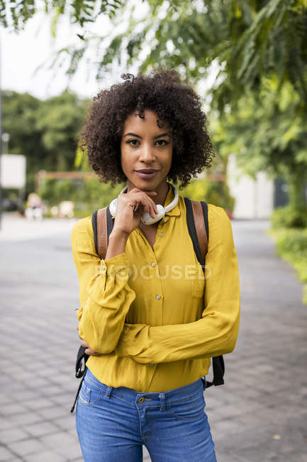 Портрет женщины в наушниках и рюкзаке на открытом воздухе — стоковое фото