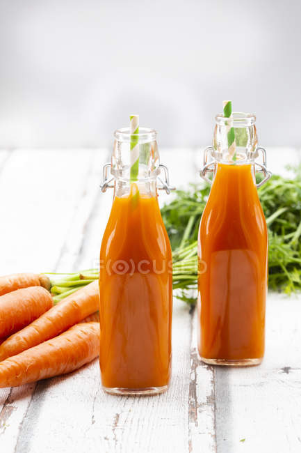 Carrots, bottles of carrot juice and swing top bottles on wood — Stock Photo