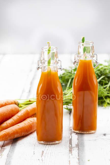 Морковь, бутылки морковного сока и качели верхней бутылки на дереве — стоковое фото