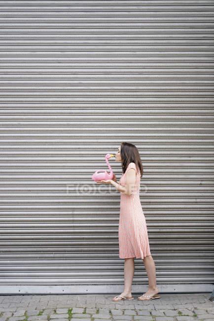 Mulher em vestido de verão com padrão de coração, kkissing figura flamingo rosa — Fotografia de Stock