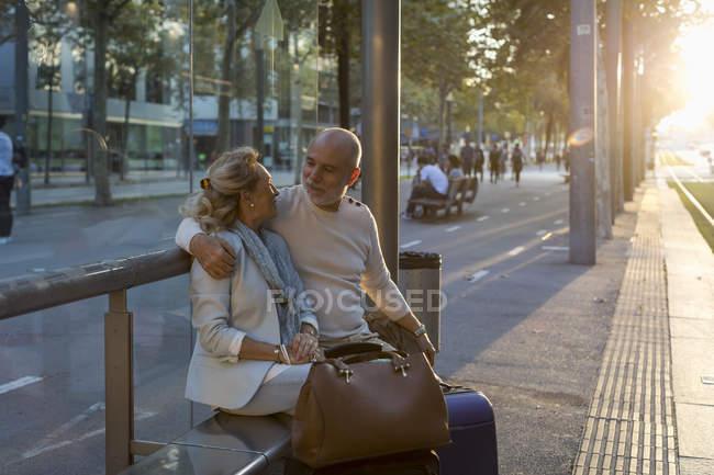 Spanien, Barcelona, älteres Ehepaar mit Gepäck sitzt bei Sonnenuntergang an der Straßenbahnhaltestelle in der Stadt — Stockfoto