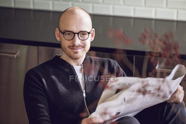 Man sitting in kitchen, reading newspaper — Stock Photo