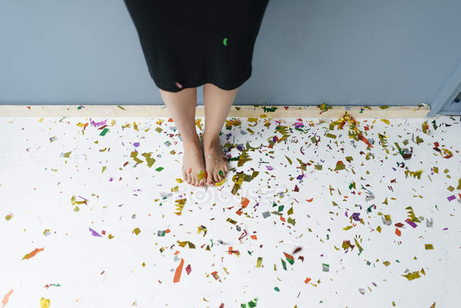 Woman standing on confetti with bare feet — стокове фото