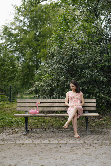 Woman sitting on park benck, talking to pink flamingo figure — Stock Photo