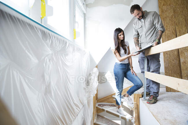 Couple in attic to be renovated looking in catalgue — Stock Photo