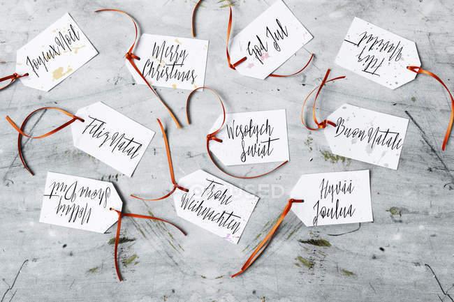 Feliz Navidad escribió en varios idiomas, Diy etiquetas de regalo - foto de stock