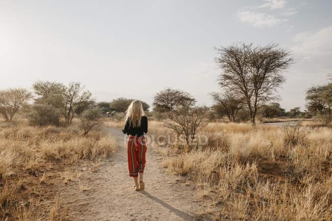 Africa, Namibia, blonde woman walking on way in grassland — Stock Photo