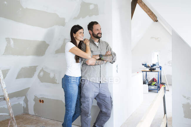 Smiling couple in attic to be renovated looking out of window — Stock Photo