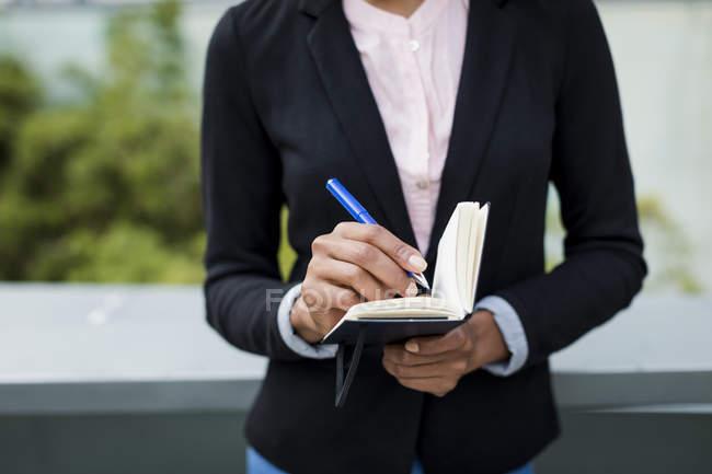 Рука бізнес-леді робить нотатки на відкритому повітрі, зблизька — стокове фото