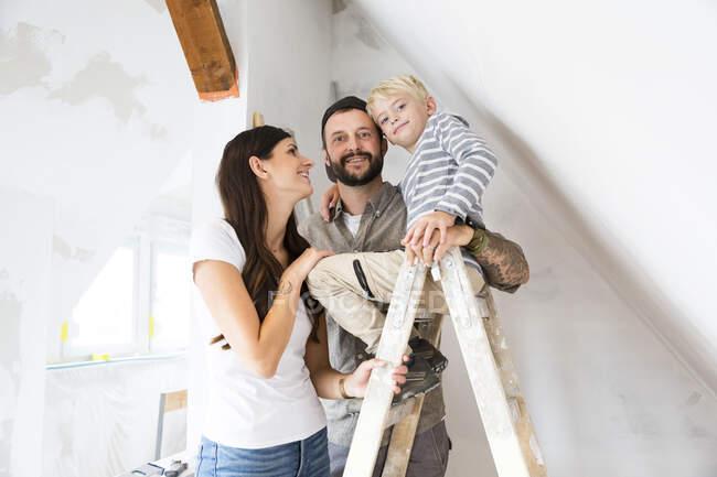 Ritratto di felice famiglia che lavora alla conversione del soppalco — Foto stock