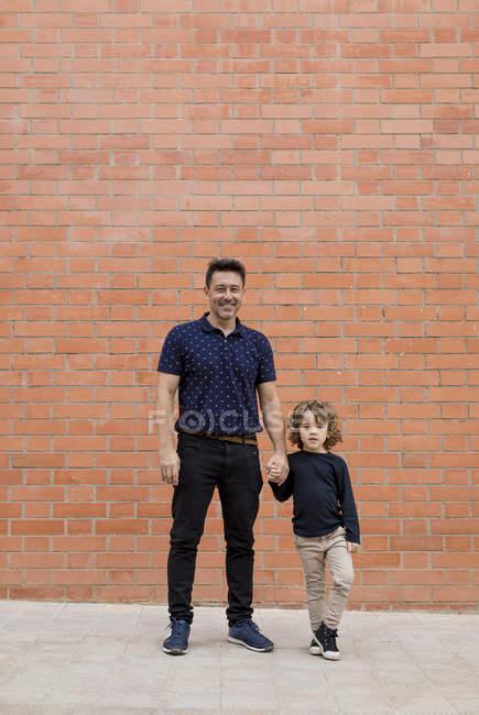 Portrait de père et fils debout main dans la main au mur de briques — Photo de stock