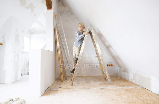 Boy standing on ladder in attic to be renovated — Stock Photo