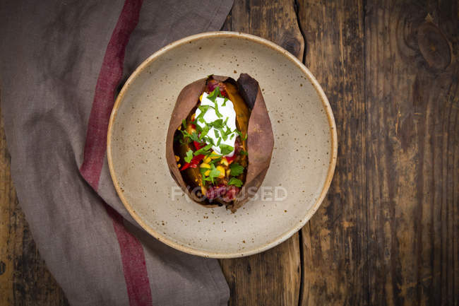 Sweet potato kumpir with chili con carne, sour cream and coriander — стоковое фото