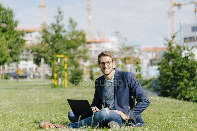 Young businessman sitting in park, using laptop — Stock Photo