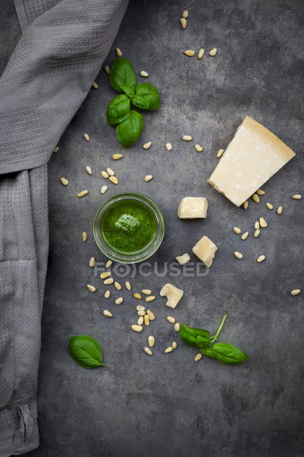 Glass of homemade pesto Genovese, pine nuts, basil leaves and parmesan on grey ground — Stock Photo