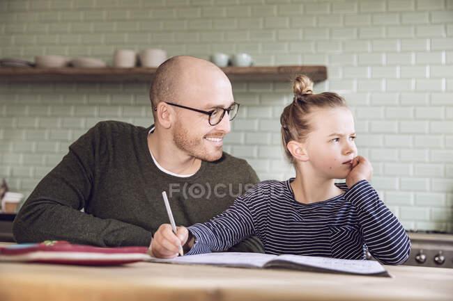 Батько з дочкою сидять на кухні і роблять домашнє завдання. — стокове фото