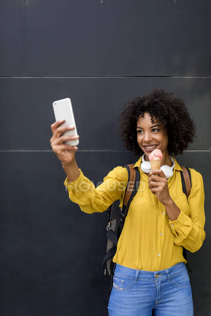 Portrait of smiling woman with ice cream cone taking selfie with smartphone — Stock Photo