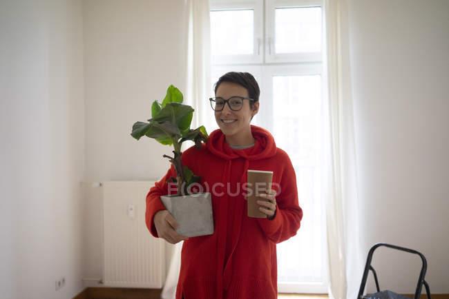 Giovane donna che si trasferisce nella sua nuova casa, portando una pianta in vaso — Foto stock