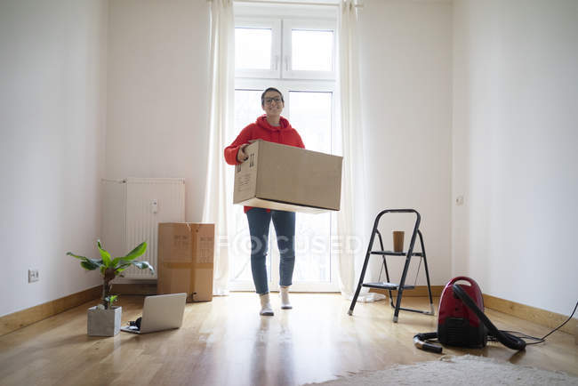 Young woman moving into her new home, carrying a cardboard box — Stock Photo