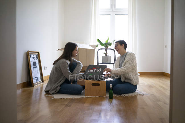 Young women sitting on floor of their new home, eating pizza — Stock Photo