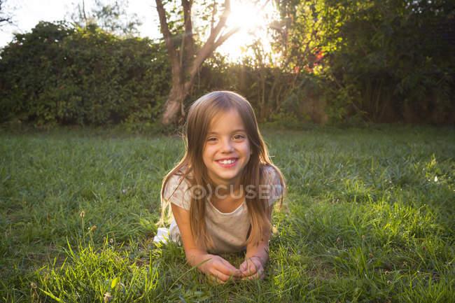 Портрет усміхненої маленької дівчинки лежачої на лузі у вечірньому сутінках. — стокове фото
