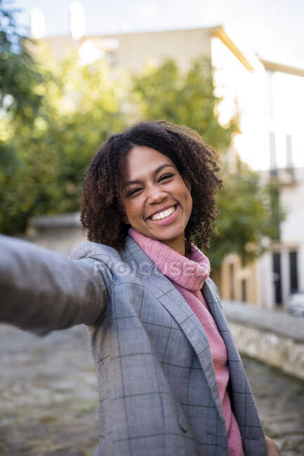 Portrait of laughing young woman raising hand — Stock Photo