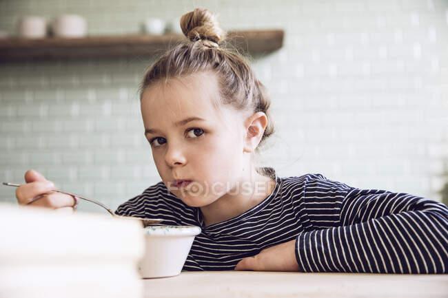 Скептическая девушка, сидящая на кухне, ест гранолу — стоковое фото