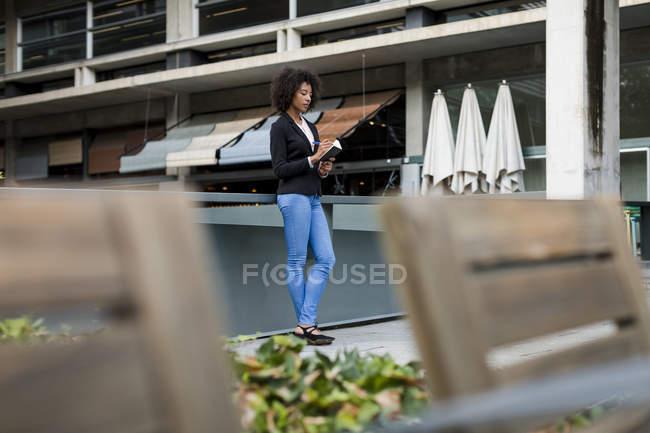Femme d'affaires debout sur la terrasse prendre des notes — Photo de stock