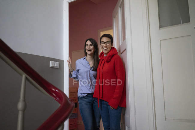 Two girlfriends at home standing in door case, with arms around — Stock Photo