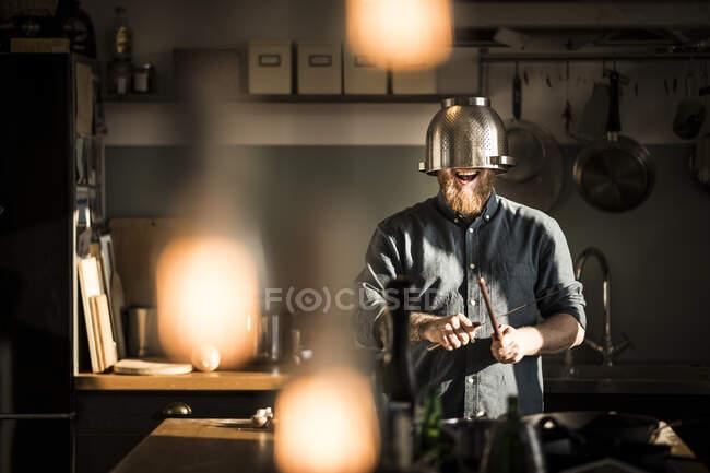 Mann schärft Küche, trägt Sieb als Helm — Stockfoto