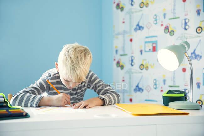 Focused boy doing homework at desk in children's room — Stock Photo