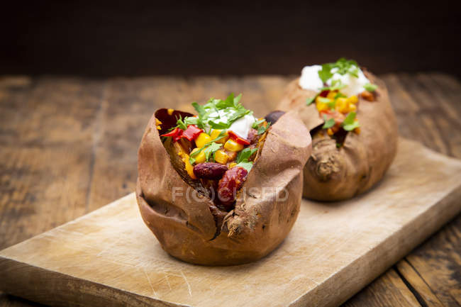 Sweet potato kumpir with chili con carne, sour cream and coriander — Stock Photo