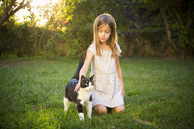 Retrato de niña acariciando gato en el jardín - foto de stock