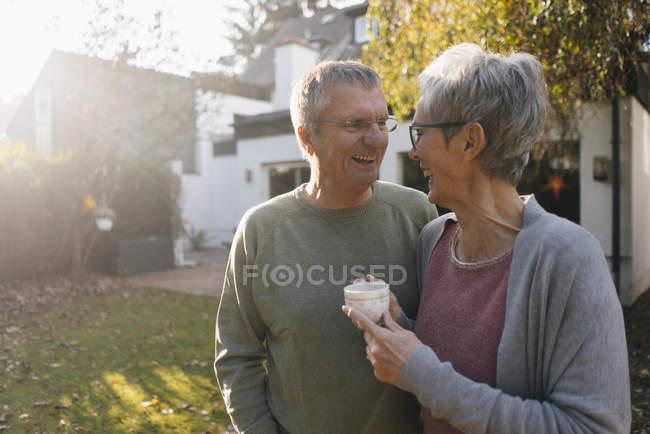 Счастливая пожилая пара с чашкой кофе в саду — стоковое фото