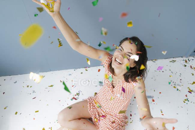 Счастливая женщина сидит на земле, бросая конфетти — стоковое фото