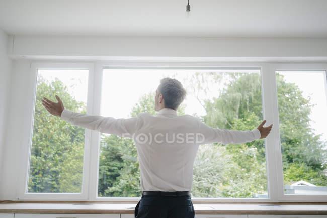 Empresário olhando para fora da janela da cozinha de sua nova casa, com os braços estendidos — Fotografia de Stock