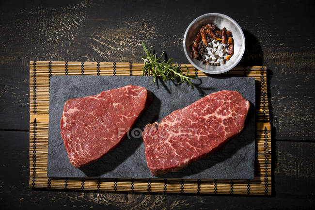 Raw beefsteaks and spices — Stock Photo