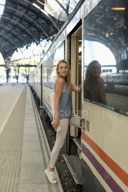 Young woman with cell phone entering a train at the train station — Stock Photo