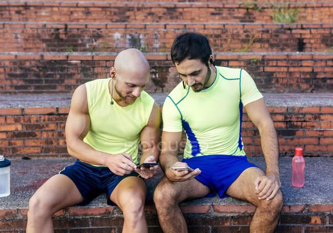 Dos atletas compartiendo teléfonos inteligentes después del entrenamiento - foto de stock