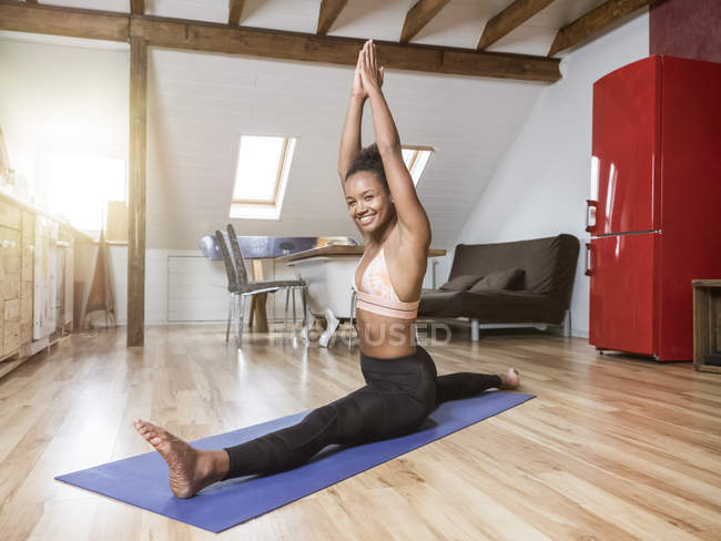 Портрет счастливой молодой женщины в позе йоги, делающей сплит — стоковое фото