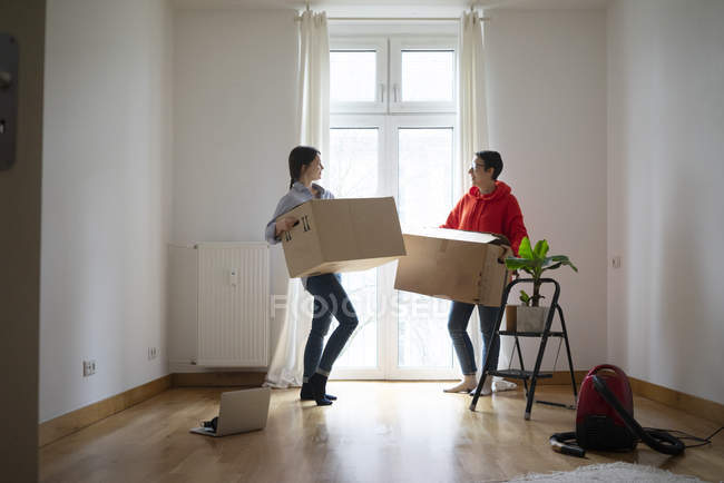 Young women moving into their new home, carrying cardboard boxes — Stock Photo
