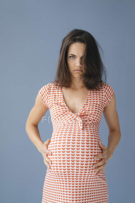 Woman pretending to be pregnant, looking angry — Foto stock
