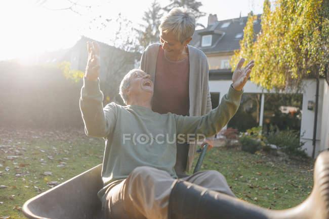 Счастливая старшая пара веселится с тачкой в саду — стоковое фото