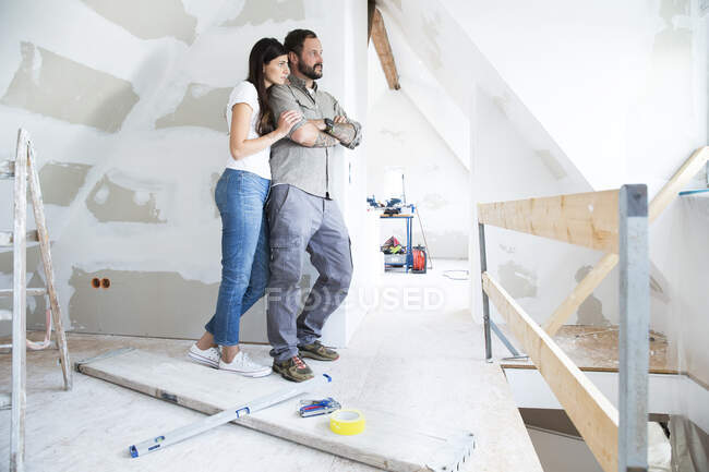Couple in attic to be renovated looking out of window — Stock Photo
