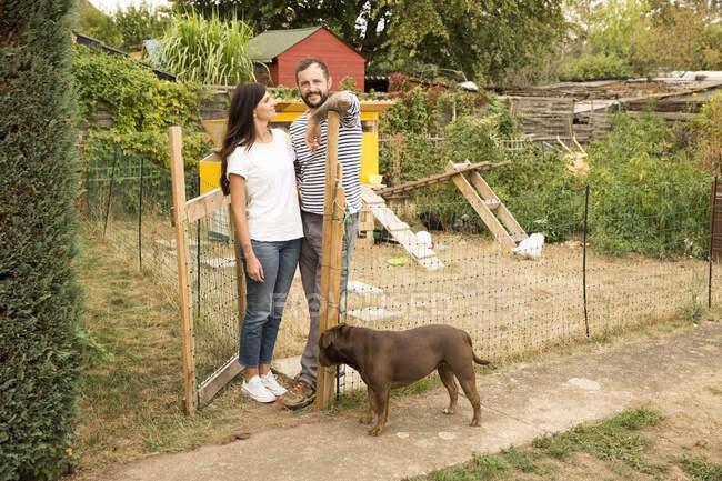 Ritratto di coppia con cane in piedi al pollaio in giardino — Foto stock